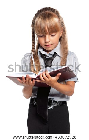 Little girl in school uniform with book, isolated on white background - stock photo