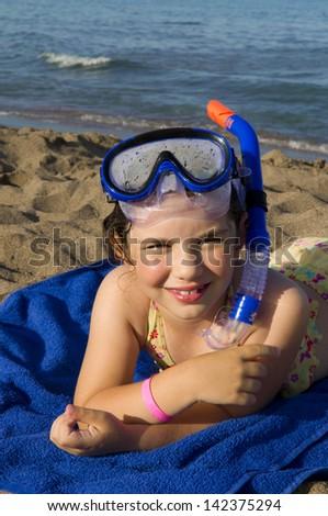 Little girl in scuba mask on the beach - stock photo