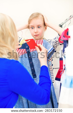 Little girl in shock looking at the price label in clothing store. - stock photo