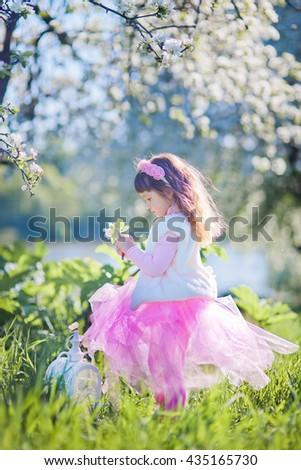 Little girl in spring blossom garden - stock photo