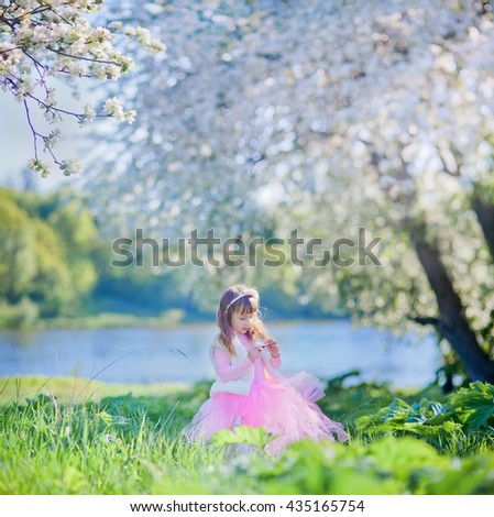 Little girl in spring blossom garden