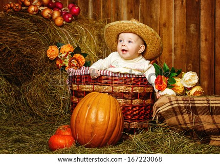 Little girl in straw hat sitting in a wicker basket near pumpkins - stock photo