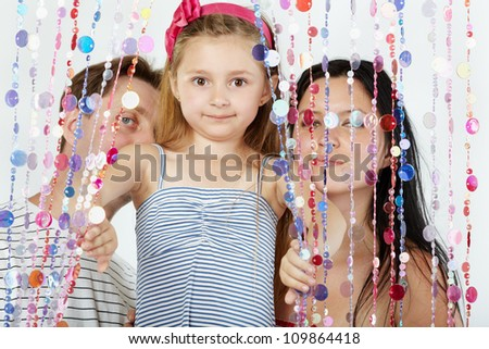 Little girl in striped sundress looks out from behind curtain of plastic beads, her parents stand behind curtain - stock photo
