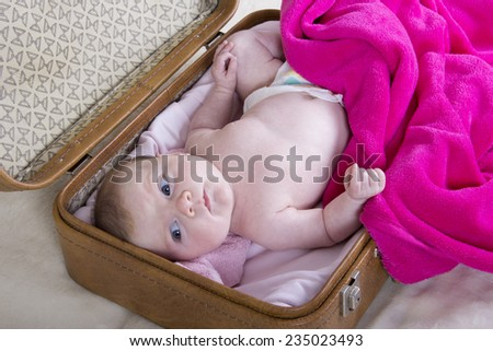 little girl in suitcase	. one month baby girl in a vintage suitcase