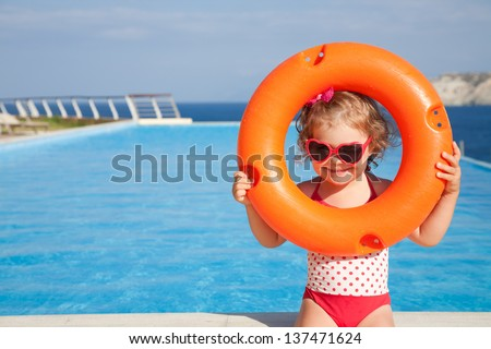 little girl in swimsuit takes lifebuoys background swimming pool - stock photo