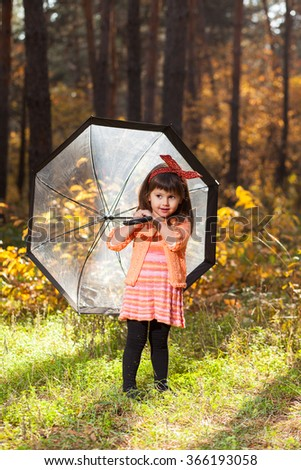 Little girl in the autumn forest with a transparent umbrella