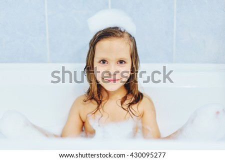little  girl in the bathroom playing with foam
