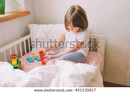 little girl in the bedroom. little girl playing with toys on the bed. cute little girl sitting on the bed in. flowers on the window. Light room.