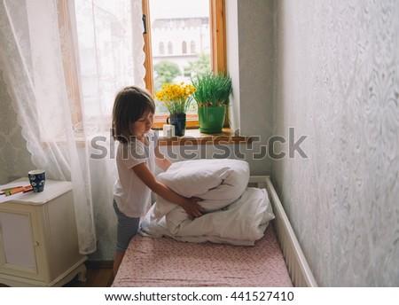 little girl in the bedroom. pretty little girl fold blanket. girl woke up. time to wake up - stock photo