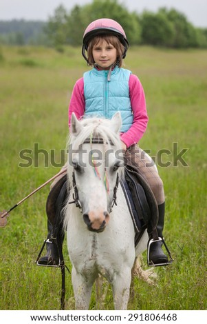 Little girl in the clothes for riding a horse sitting Sharpness on the girl  Outdoors - stock photo