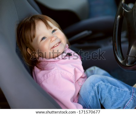 Little girl in the driver's seat of a car