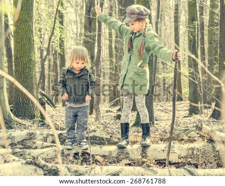 little girl in the forest with her sister. Photo in retro style - stock photo