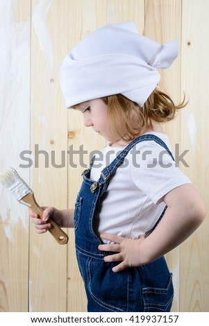 Little girl in the form of a painter paints a wooden wall in white