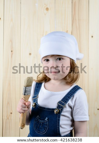 Little girl in the form of a painter with a brush in his hands posing on the background of wooden wall