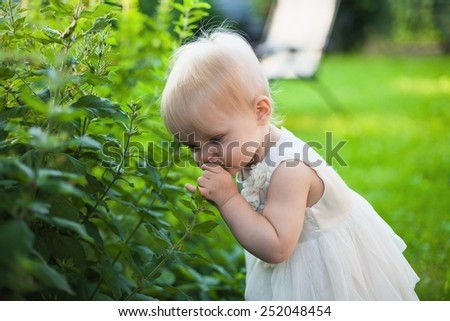 little girl in the garden tears and sniffs flowers on a sunny summer day - stock photo