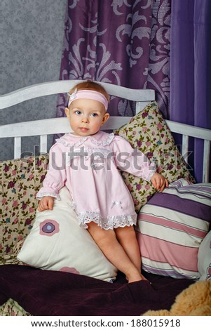 Little girl in the nursery stands leaning on pillows on a cot - stock photo