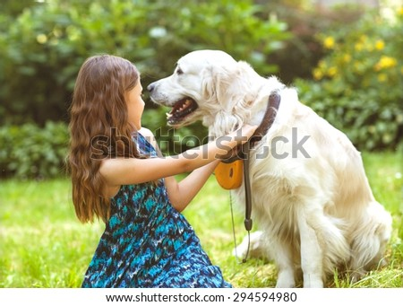 little girl in the park their home with a dog - stock photo