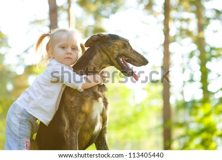 little girl in the park with a dog - stock photo