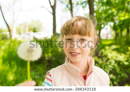 little girl in the park with dandelion