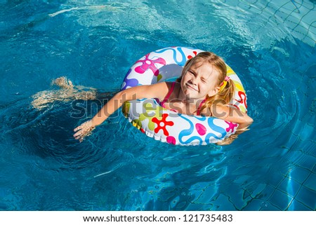 little girl in the pool  with rubber ring