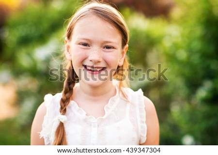 Little girl in the spring garden at sunset, close up portrait - stock photo