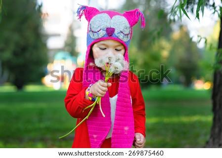 Little girl in the summer park holding a dandelion. - stock photo