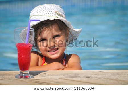 Little girl in the swimming pool with cocktail
