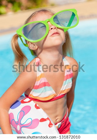 little girl in the swimming pool  with rubber ring - stock photo
