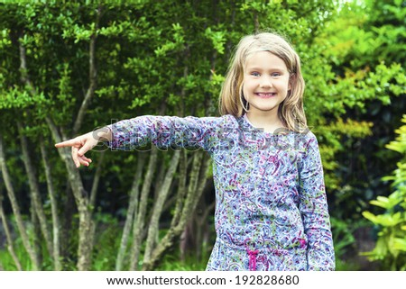 Little Girl in the Woods showing something - stock photo