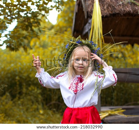 Little girl in ukrainian clothes shows something with her finger - stock photo