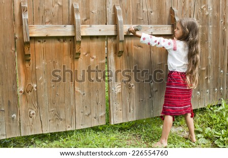 Little girl in Ukrainian national dress opens the gate - stock photo