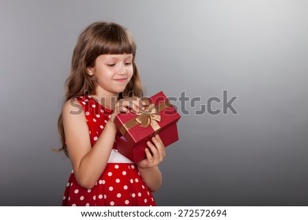 Little girl in vintage spotted red dress holding her present - stock photo