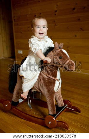 little girl in vintage white dress on the rock horse - stock photo