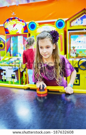 Little girl in violet suit plays air hockey - stock photo