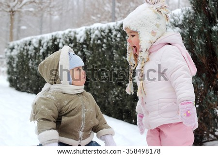 Little girl in warm coat and knitted hat has a fun in the winter forest and shows her toddler brother how to catch snowflakes with the mouth, outdoor winter concept - stock photo
