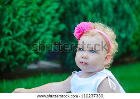Little girl in white dress and ping band with flower