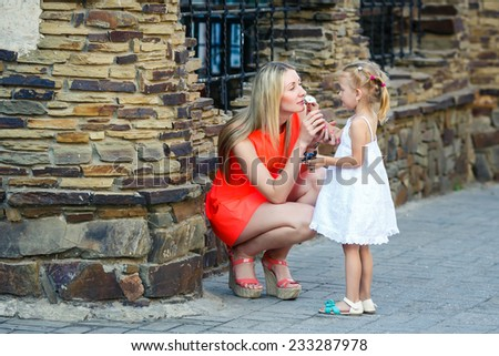 Little girl in white dress gave a flower to young blonde woman in red short dress. - stock photo