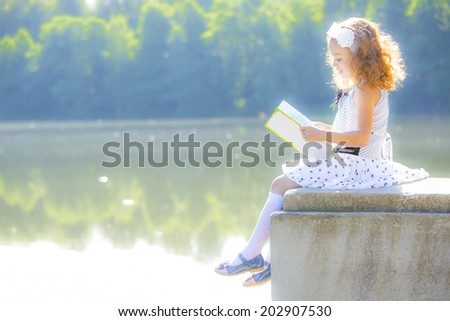 Little girl in white dress reading a book by the lake - stock photo