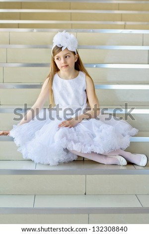 Little girl in white dress, shoes and tights posing on the steps - stock photo