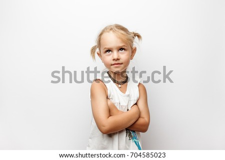 Little girl in white dress with crossed arms looks up on white background