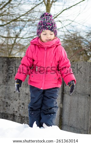 Little girl in winter clothes is playing in snow with snow on her winter gloves