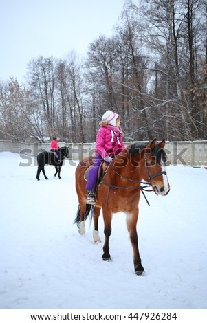 Little girl in winter clothes sitting on horseback in front of another rider - stock photo