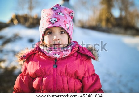Little girl in winter clothes standing in mountain ski resort. A child with cap, scarf and winter jacket is looking at the camera outside in snowy nature. - stock photo