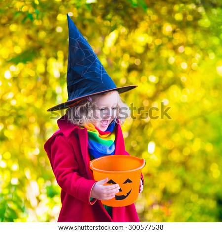 Little girl in witch costume playing in autumn park. Child having fun at Halloween trick or treat. Kids trick or treating.  Toddler kid with jack-o-lantern. Children with candy bucket in fall forest. - stock photo