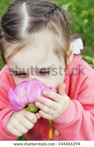 Little girl inhales the scent of a peony flower - stock photo