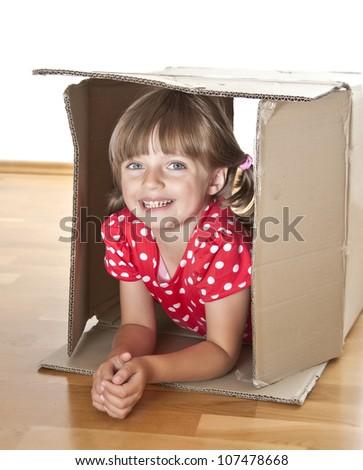 little girl inside a cardboard box - stock photo