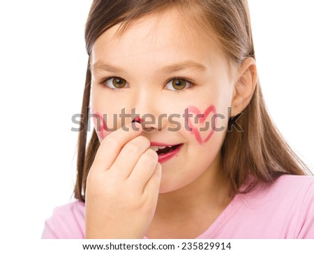 Little girl is applying lipstick on her cheek and nose, isolated over white - stock photo
