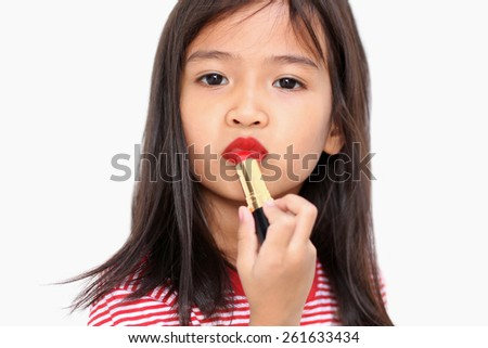 Little girl is applying lipstick on her mouth isolated over white - stock photo