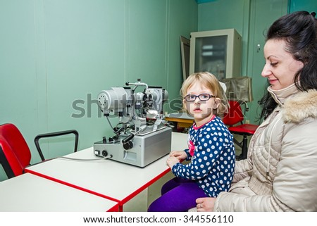 Little girl is at the eye examination showing directions of signs on board.