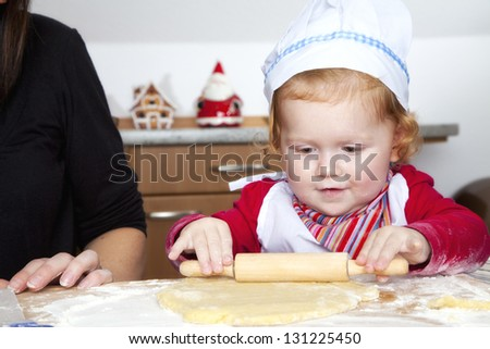 Little girl is baking in the kitchen. She has many fun. - stock photo